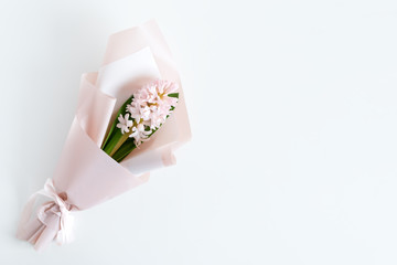 Spring flowers. Fresh bouquet with hyacinth in minimal style on light background. Top view, spring flat lay with copyspace for text. Love and gift concept