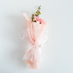 Spring flowers. Fresh bouquet with carnation in minimal style on light background. Top view, spring flat lay. Love and gift concept