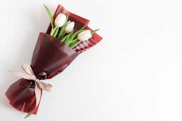 Spring flowers. Fresh tulips bouquet in minimal style on light background. Top view, spring flat lay with copyspace for text. Love and gift concept