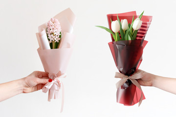 Woman hands with manicure holding spring flowers. Fresh bouquets with hyacinth and tulips. Love and gift concept.