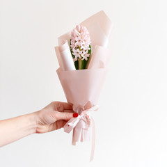 Woman hand with manicure holding spring flowers. Fresh bouquet with hyacinth. Copyspace for text. Love and gift concept.