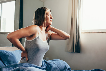 Woman with back pain sitting on her bed