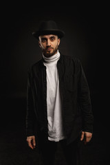 Attractive young bearded man in black shirt and hat