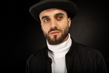 Close up portrait of young model male with beard in black hat