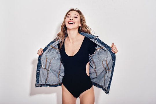 Laughter is the best medicine. Seductive young lady in bodysuit and denim jacket is laughing while standing over white background