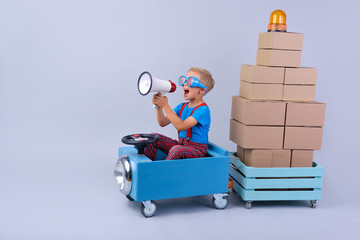 Smiling boy driving blue, fanny car and wagon with small boxes.Happy child with paper boxes on grey background. Studio shot. Delivery, shipping,  transport and supplier concept.