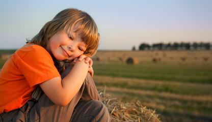 boy in a haystack in the field