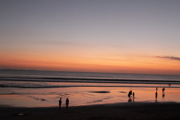 people on beach at sunset