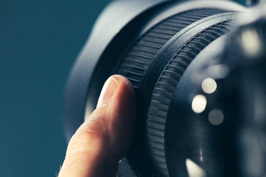 Photographer using zoom lens on DSLR camera
