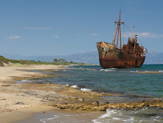 Fotobehang Schip Rusty big ship shipwreck on Selinitsa beach under a deep blue sky at Gytheio Greece.