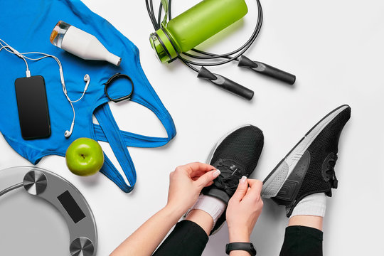 Overhead view of woman hands tying shoes with sport equipments on white background
