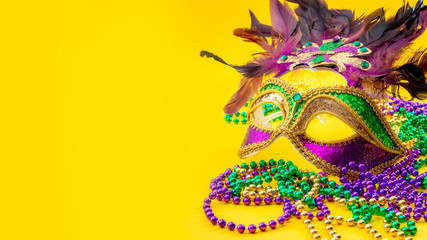 Happy Mardi Gras and Fat Tuesday carnival concept with close up on a face mask full of color, feathers and texture and golden, green and purple beads isolated on yellow background with copy space Fotomurales
