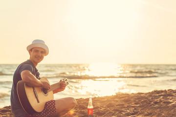 Tuinposter Art Studio Young man play guitar on the beach