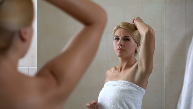 Woman looking at armpit, low quality depilation, bad smell, cheap antiperspirant