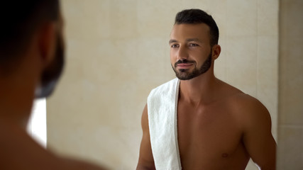Topless man with towel looking in mirror, confident businessman in morning