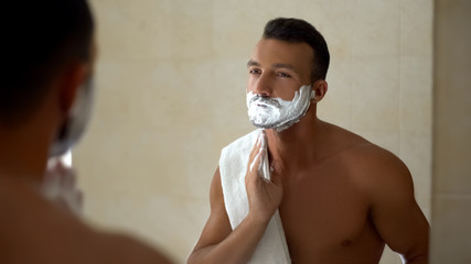 Man applying shaving cream to face and beard, ready to change appearance, style