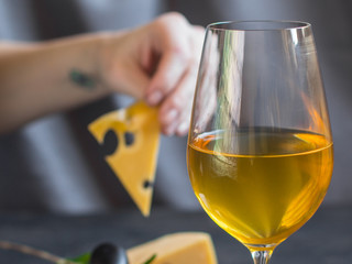 white wine in a transparent glass and snack. food background. top photo