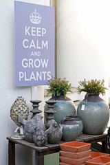 """Stone birds, ceramic vases, flower pots standing on a wooden table and hanging picture """"Keep calm and grow plants"""" in a flower shop"""