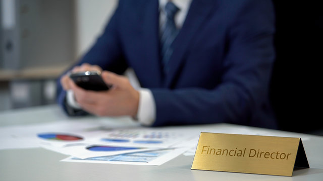 Male financial director sending report online via e-mail on smartphone, work