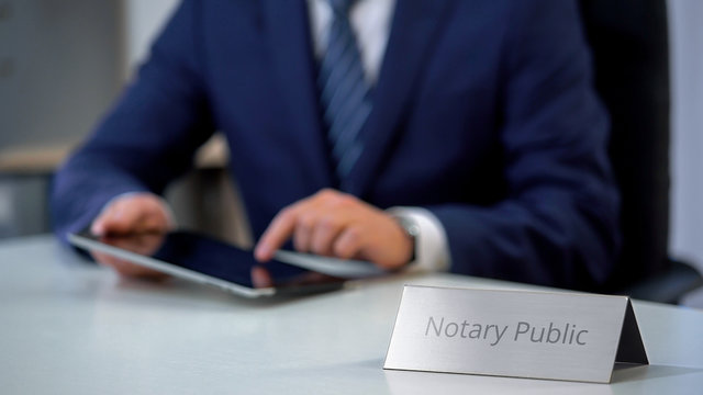 Young notary public working on tablet pc, preparing administrative documents