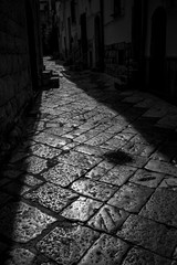 Beautiful Sun-lit stone narrow street in Altamura, Apulia, Italy. Black and white high contrast photograph taken against the Sun light in sunny summer afternoon in the old center of the stunning town