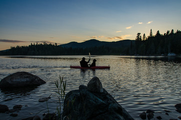 silhouette of man and dog in kayak at sunset