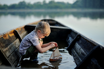 The child is playing with a small boat. Children's imagination. Dreams of a small child.