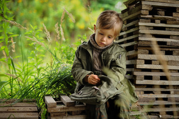 A small sad boy dressed in a military dress is resting after a trip