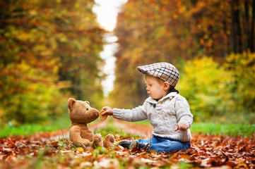 Child and autumn. Little boy gives a cookie to a teddy bear. They both sit on a forest path among autumn colored leaves and trees.