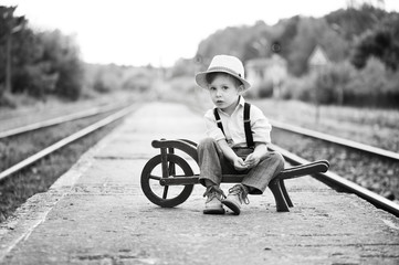 Monochrome portrait of cute boy wearing in retro style sitting on railway station and is waiting for something.