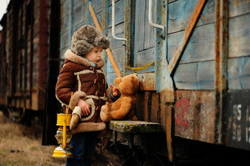 Little boy is wearing a sheepskin coat and fur hat holding an oil lamp and playing with a teddy bear at a railway station