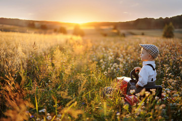 A little boy sits on a tractor and looks at a beautiful valley with cereals and flowers. Sunset, idyll in the countryside. small farmer in the field.