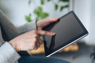 Woman holding her forefinger on tablet display