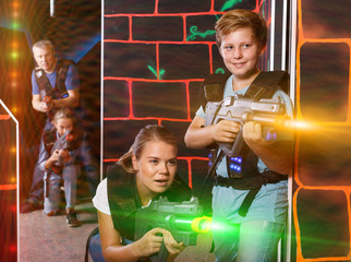 Smiling boy and his mother aiming laser guns