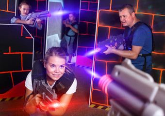 attractive girl with laser pistol playing laser tag with friends