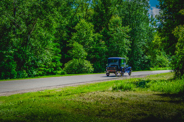 Blue antique car on a winding road through trees