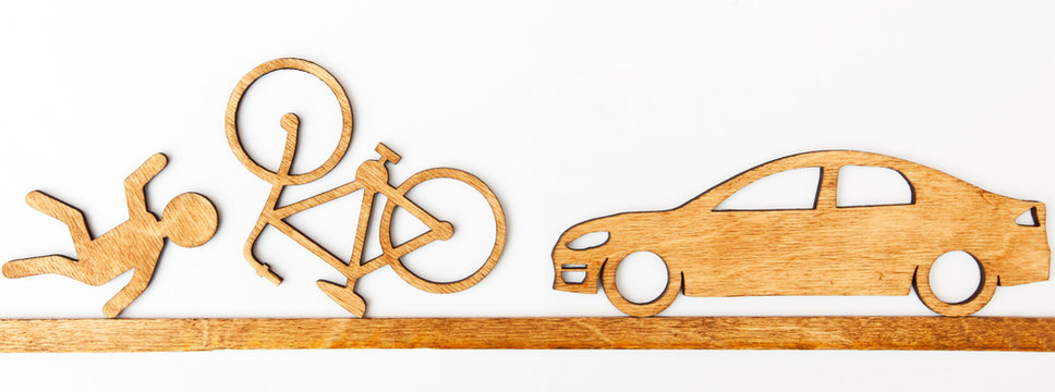 Wooden toy little man and car and bicycle on white background. Concept  car accident with cyclist