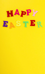 Easter concept. Inscription in colored letters Happy Easter on a yellow background.Top View. Flat Lay
