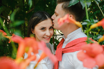 A beautiful couple kisses under a green background of nature.