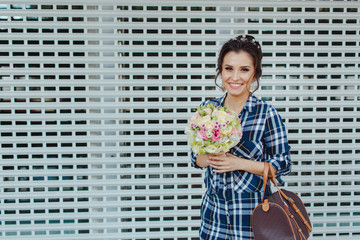 A happy smiling girl poses with a bunch of flowers in her hands at an open background
