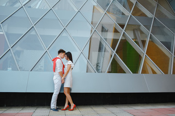 Young happy couple standing over glass of window background.