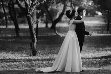 Wedding couple embracing a green park in daylight.