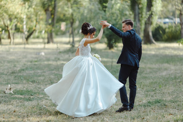 Wedding couple dancing in a green and beautiful park.