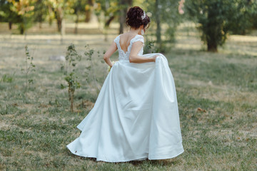 A happy bride dancing in a green park backgraound.