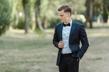 Portrait of a stylish man in a black suit in a park.
