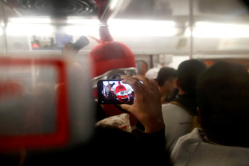 A passenger takes a photo of a man wearing a costume, representing a condom, inside a metro car, on the International Condoms Day, celebrated a day before Valentine Day, in Mexico City