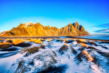 Sunset over the Stokksnes Mountain on Vestrahorn Cape with Snow in Iceland