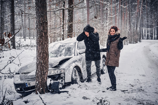 The guy is shocked by the fact that his girl crashed his car. The car got into a skid and crashed into a tree on a snowy road.