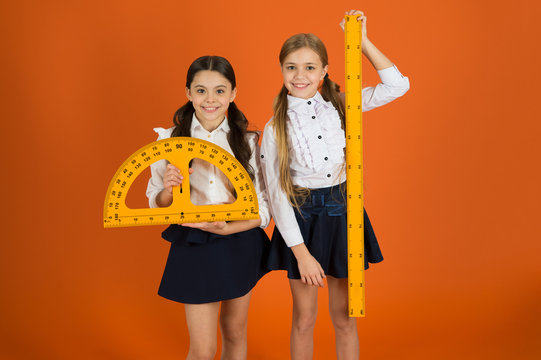 Pupil cute girls with big rulers. Geometry favorite subject. Education and school concept. School students learning geometry. Kids school uniform on orange background. STEM school disciplines