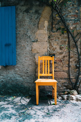 France, Grignan, yellow wooden chair in front of an old house